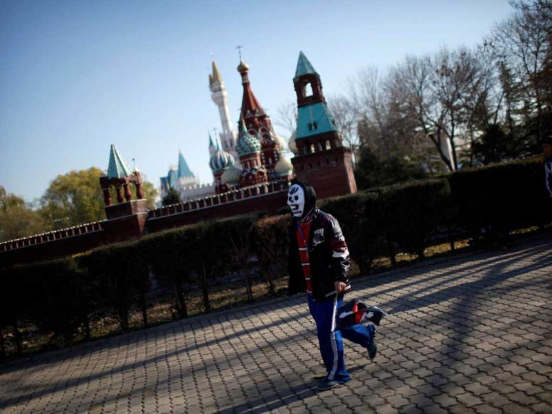A student wearing a mask walks past the mini replica of the Kremlin in Beijing World Park, in the southwestern suburb of Beijing. Photo: AFP