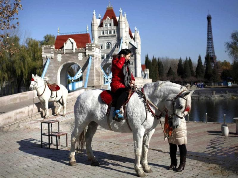 A tourist rides a horse before the mini replicas of London Bridge and the Effiel Tower in Beijing World Park, in the southwestern suburb of Beijing. Photo: AFP