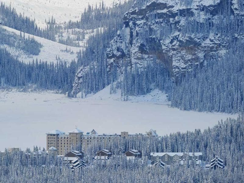 Jamie, hotel worker, of Fairmont Chateau Hotel shovels a snow between the hotel and a gateway to the Lake Louise early morning in Lake Louise, Alberta.  AFP Photo