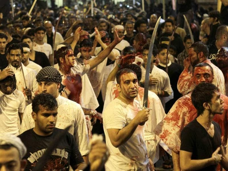 Bahraini Shiite Muslim worshippers, stained by their own blood from self inflicted wounds, hold swords in Manama, Bahrain, during a procession to mark the holy month of Muharram, when Shiites mourn the killing of Imam Hussein, grandson of Islam's 7th-century founding Prophet Muhammad. AP Photo