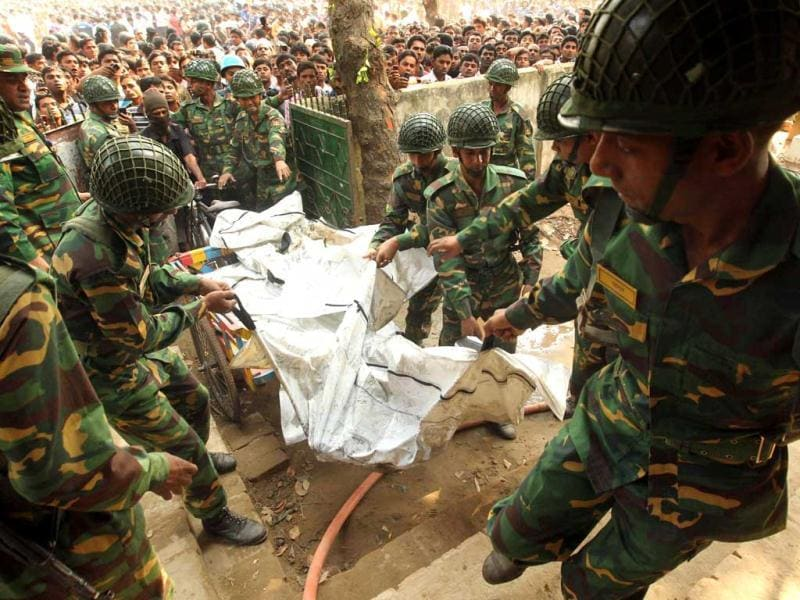 Bangladeshi Army personel carry the bodies of victims who died in a fire in the nine-storey Tazreen Fashion plant in Savar, about 30 kilometres north of Dhaka. AFP Photo