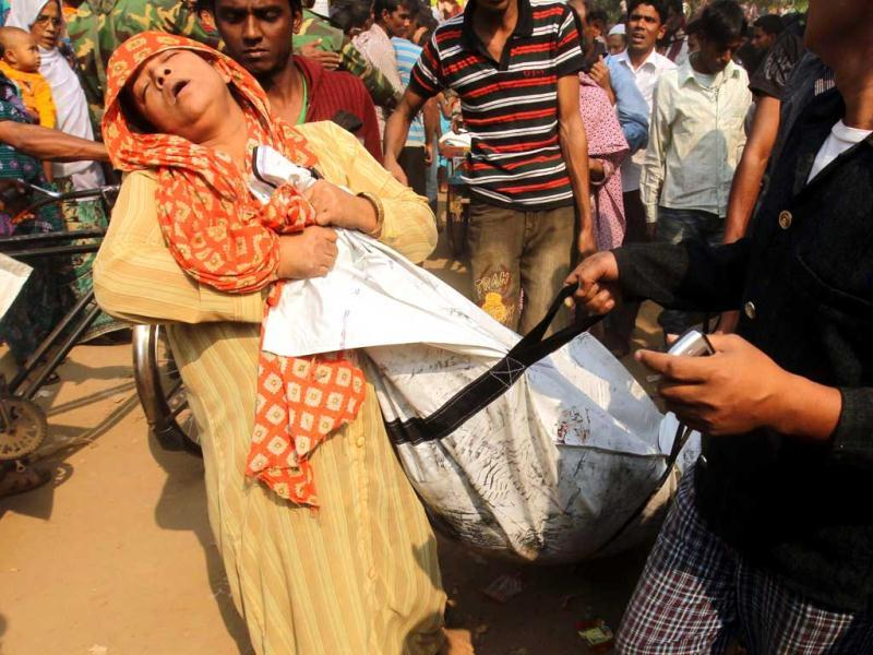 Bangladeshi women mourns as she holds the body of a relative who died in a fire in the nine-storey Tazreen Fashion plant in Savar, about 30 kilometres north of Dhaka. AFP Photo