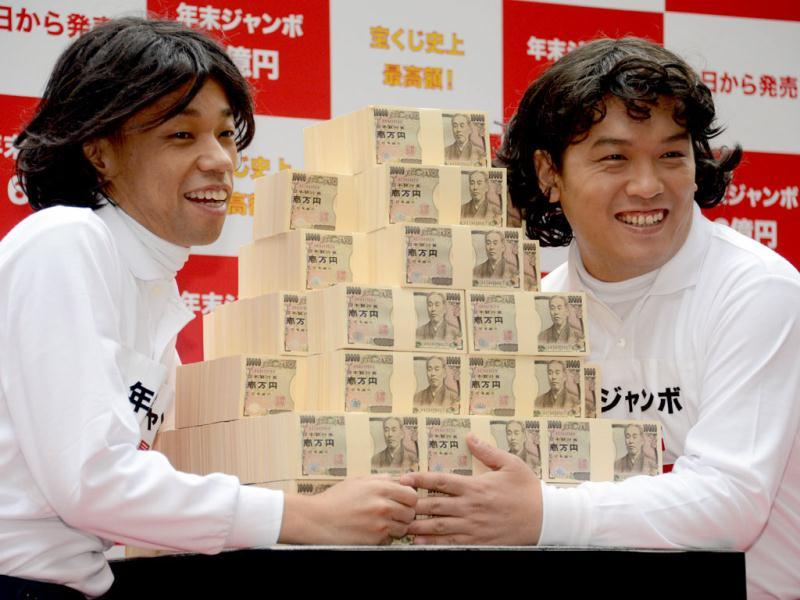 Japanese comedians Kenji Tada (L) and Yoshi Yamada pose with 600 million yen ($7.3 million) for the year-end Jumbo Lottery as the the first tickets went on sale in Tokyo. AFP Photo