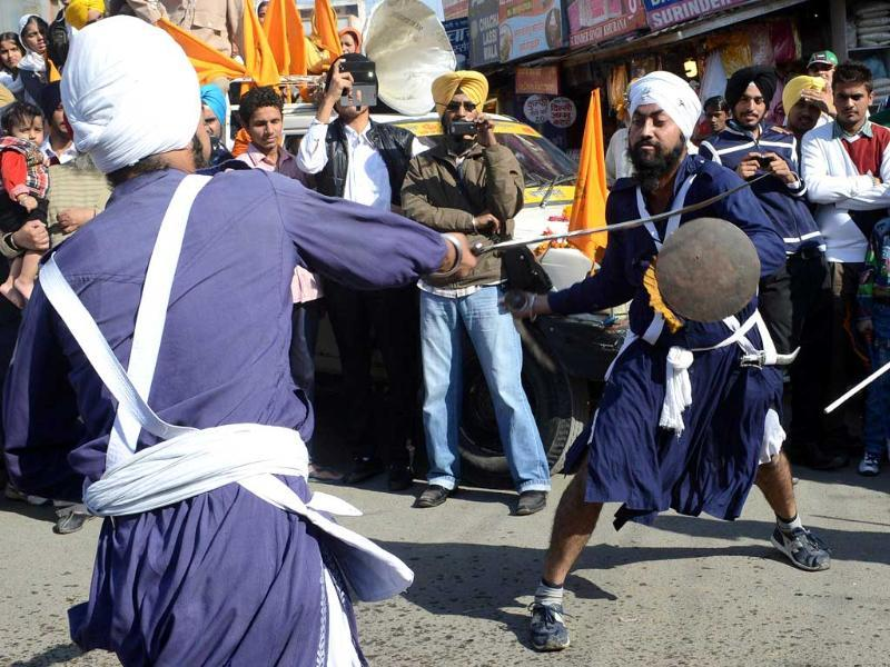 Sikh Nihangs - warriors - demonstrate their 'gatka' skills during a procession from Sri Akal Takhat to the Golden Temple in Amritsar on the eve of the 543rd birth anniversary of Sri Guru Nanak. AFP Photo/Narinder Nanu