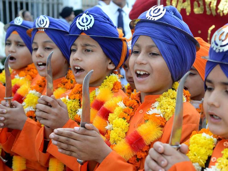 Sikh boys dressed as Punj Pyara raise slogans during a procession at The Sikh Shrine Golden Temple in Amritsar on the eve of the 543rd birth anniversary of Sri Guru Nanak. AFP Photo/Narinder Nanu