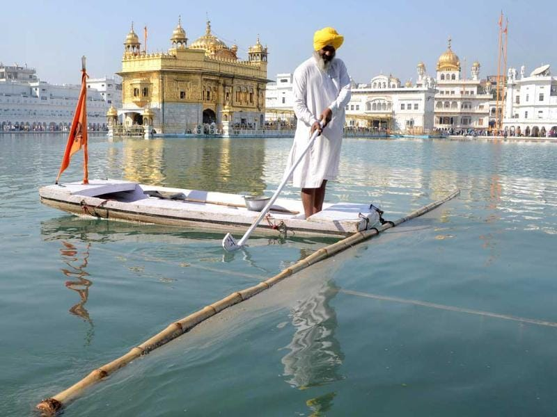A Sikh devotee cleans the sarover - water tank - at The Sikh Shrine Golden Temple in Amritsar on the eve of the 543rd birth anniversary of Sri Guru Nanak Dev. AFP Photo/Narinder Nanu