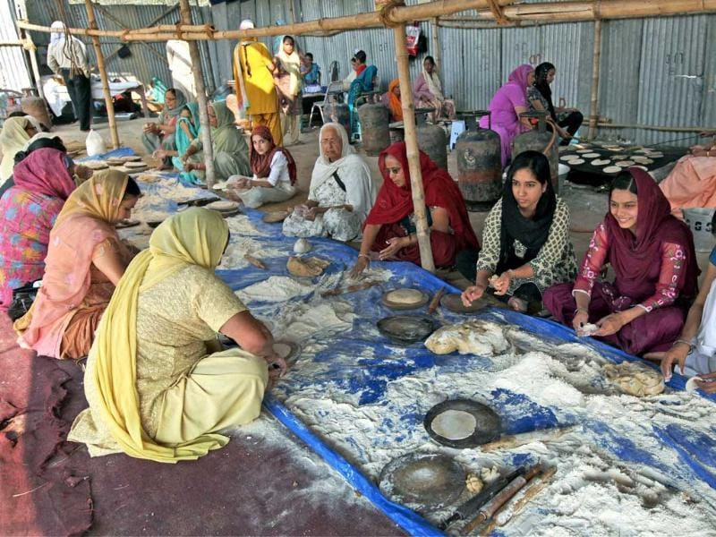 Sikh women prepare 'Chapati' for 'langar' on the eve of Guru Nanak Devji's birth anniversary in Kolkata. PTI Photo/Swapan Mahapatra