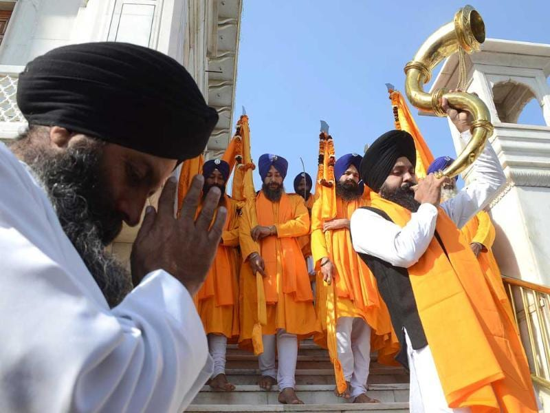 A Sikh devotee plays a musical instrument as he walks with Punj Pyara holding flags of the Sikh religion as they escort a procession from Sri Akal Takhat at The Golden Temple in Amritsar on the eve of the 543rd birth anniversary of Sri Guru Nanak. AFP/Narinder Nanu