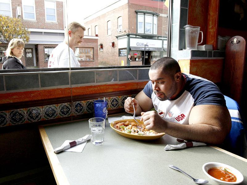 Moustafa Ismail eats lunch at his favorite Mexican restaurant after his daily workout at World Gym in Milford, Mass. AP Photo
