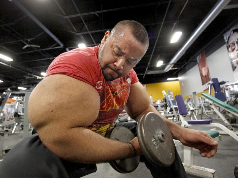 Moustafa Ismail lifts free weights during his daily workout at World Gym in Milford, Mass. AP Photo