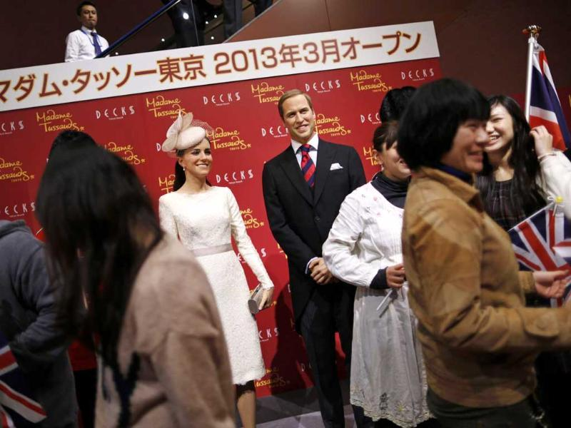 Guests holding Union Flags prepare for a photo session with wax figures of Britain's Prince William and his wife Catherine, Duchess of Cambridge, during a media briefing for the opening of the Madame Tussauds Tokyo wax museum, in Tokyo. Reuters/Issei Kato