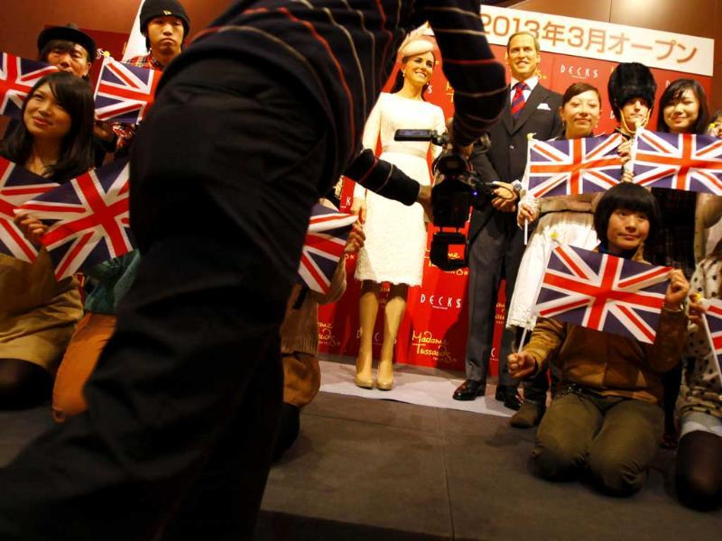 A video photographer shoots after an unveiling ceremony of wax figures of Britain's Prince William and his wife Kate, the Duchess of Cambridge in Tokyo. AP Photo/Junji Kurokawa