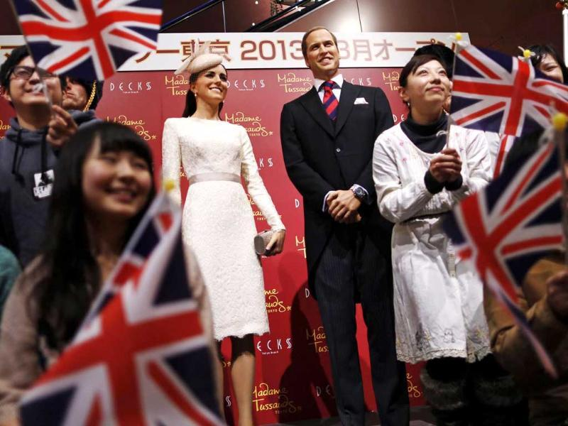 Guests wave Union Flags as they pose with wax figures of Britain's Prince William and his wife Catherine, Duchess of Cambridge, during a media briefing for the opening of the Madame Tussauds Tokyo wax museum, in Tokyo. Reuters