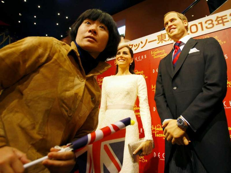 A visitor walks by wax figures of Britain's Prince William and his wife Kate, the Duchess of Cambridge in Tokyo. AP Photo/Junji Kurokawa