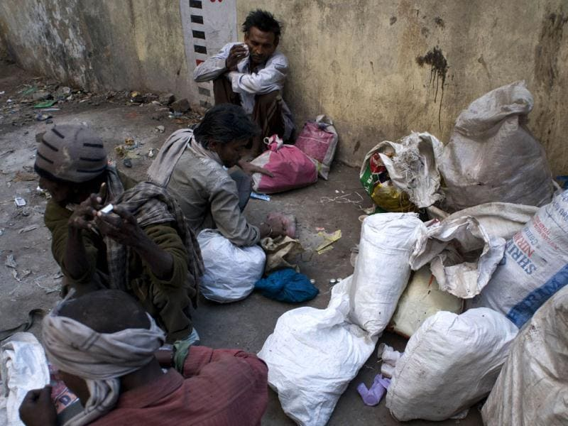 Drug users sort out recycling wastes which pays for their habit in the old sector of New Delhi. AFP/Anna Zieminiski