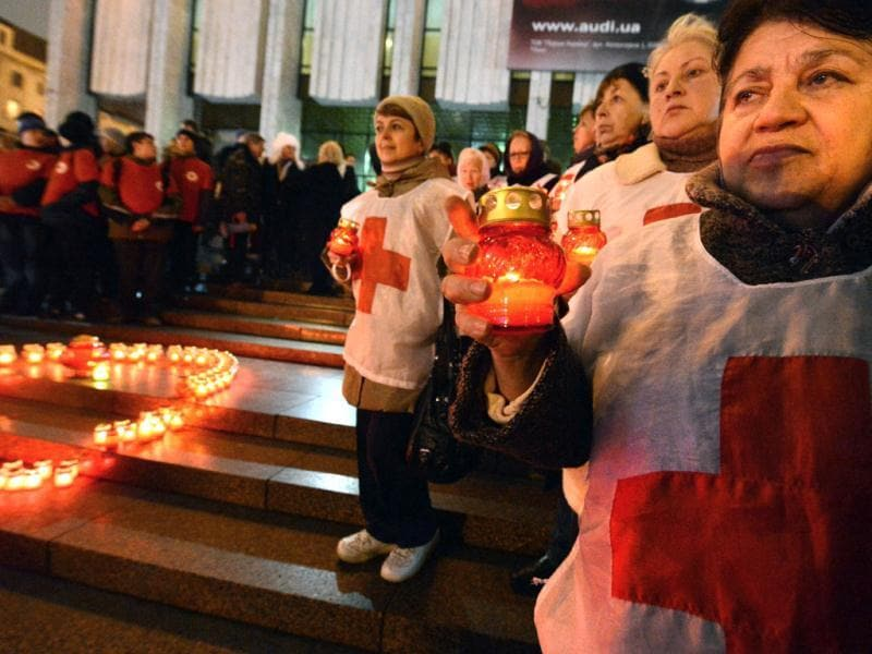 Activist of public organizations and HIV infected people hold candles as they rally in front of a Red Ribbon set with candles in the center of the Ukrainian capital of Kiev. AFP/Sergei Supinsky
