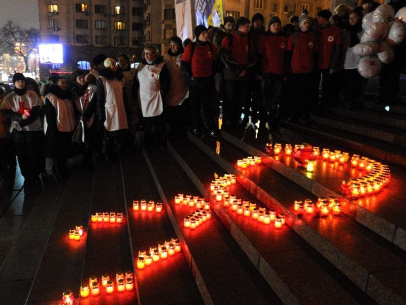 Ukrainian people make a red ribbon sign with candles ahead of the World AIDS Day, in Kiev, Ukraine. AP/Sergei Chuzavkov