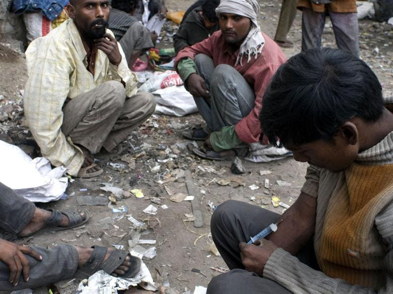 An addict injects drugs in the old sector of New Delhi. AFP/Anna Zieminiski