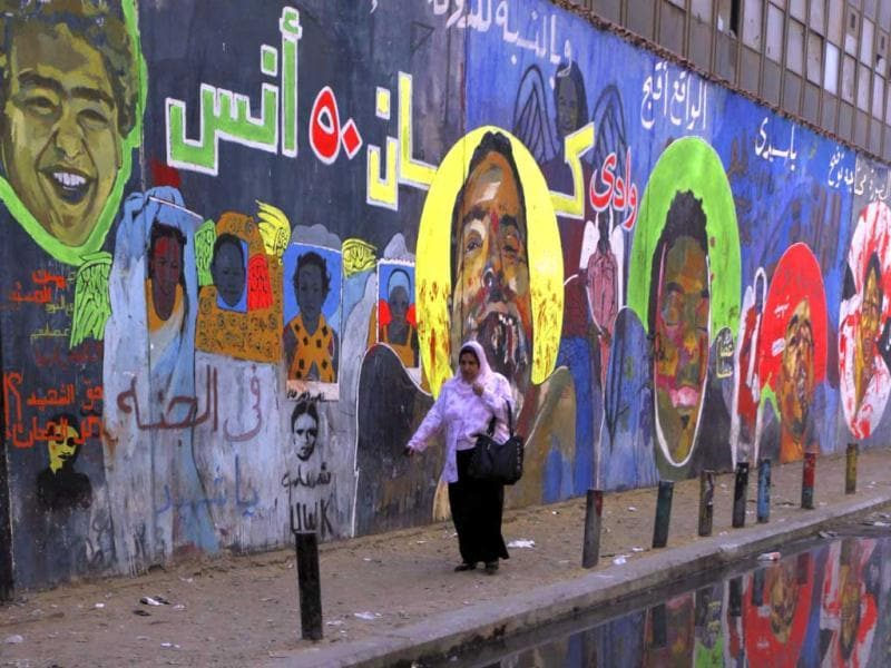 A woman walks past a mural-covered wall at Mohamed Mahmoud street in Cairo. Reuters/Amr Abdallah Dalsh