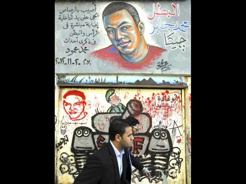 People walk past a mural showing youth activst Gaber Salah, also known as Gika, who died after he was shot during clashes with riot police last week, at Mohamed Mahmoud street in Cairo. Reuters/Amr Abdallah Dalsh