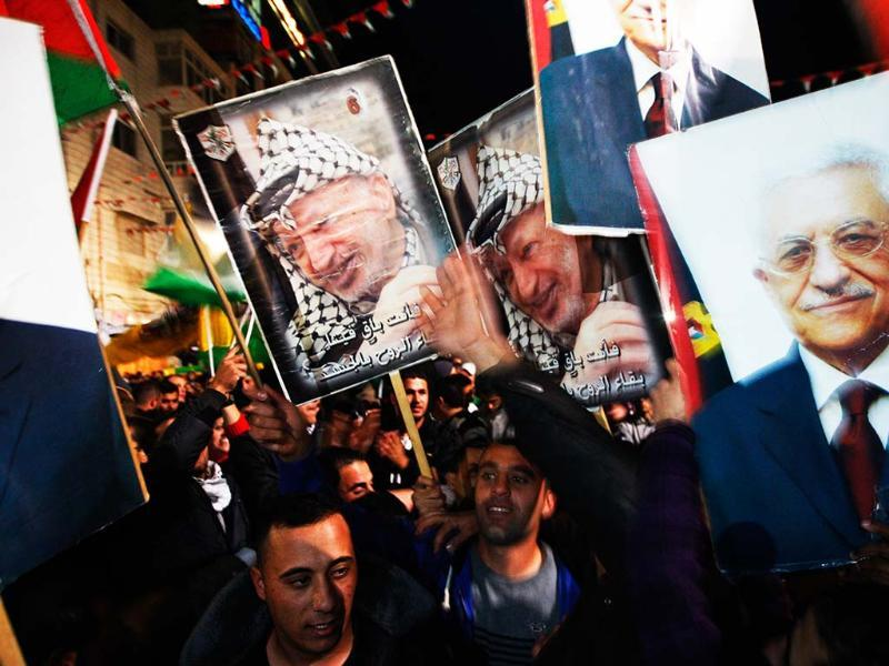 Palestinians celebrate as they wave posters of former Palestinian leader Yasser Arafat, left, and President Mahmoud Abbas, right, as they watch the UN General Assembly votes on a resolution to upgrade the status of the Palestinian Authority to a nonmember observer state, in the west bank city of Ramallah. AP