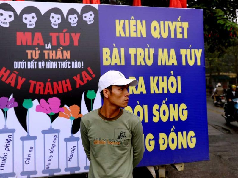 A man stands next to a poster warning that drug using is leading to HIV affection at the venue of a meeting on World's AIDS Day in Hanoi. AFP
