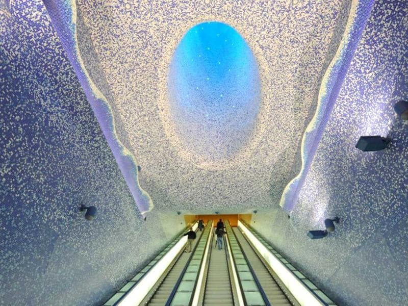 People walk in the 'Cathedral' with the Crater of Luz by artist Oscar Tusquet Blanca in the Toledo subway station as part of the 'Art Station Line 1' project in Naples. AFP