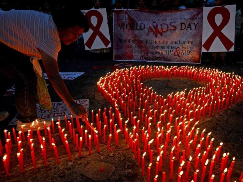 An AIDS activist lights a group of candles placed in the shape of a red ribbon during an event marking World Aids Day in Manila. AFP Photo