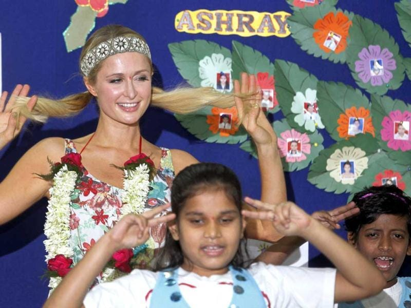 Paris Hilton, left, dances with children during her visit to Ashray, an orphanage in Mumbai. (AP Photo)
