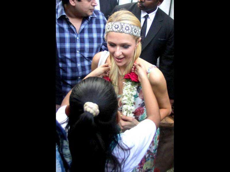 American socialite, businesswoman and fashion designer, Paris Hilton is garlanded by a girl during her visit to an orphanage in Mumbai. (PTI Photo)