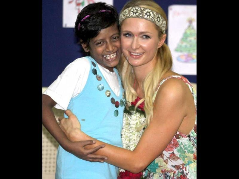 American socialite, businesswoman and fashion designer, Paris Hilton hugs a girl during a visit to an orphanage in Mumbai. (PTI Photo)