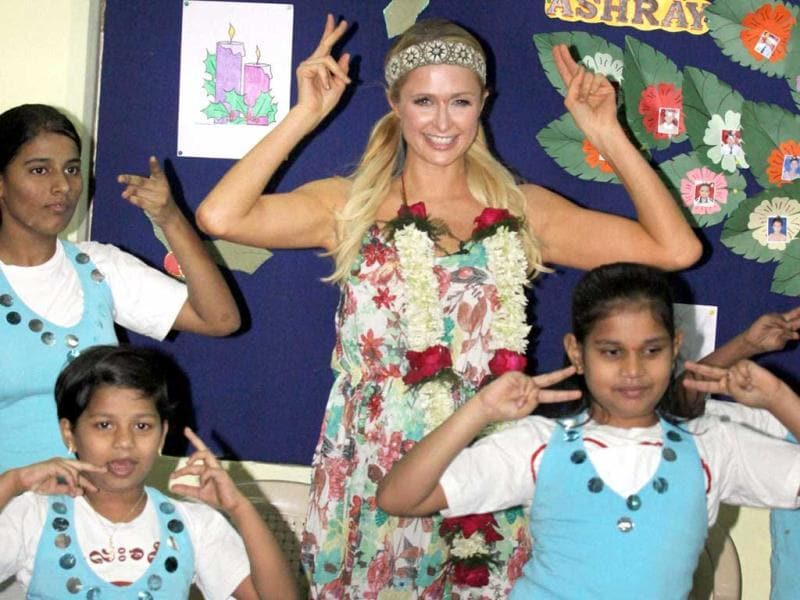 Paris Hilton shakes a leg with children during her visit to an orphanage in Mumbai. (PTI Photo)