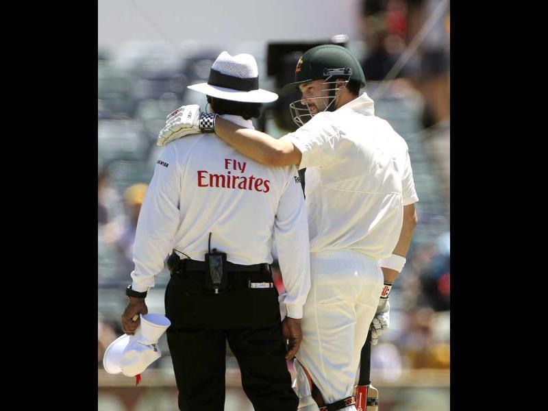 Australia's Ed Cowan chats with umpire Asad Rauf on day four of the third cricket test match against South Africa in Perth, Australia. AP Photo