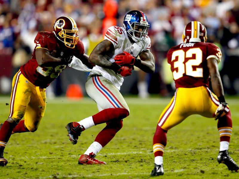 Martellus Bennett #85 of the New York Giants catches a pass and runs against linebacker London Fletcher #59 and Jordan Pugh #32 of the Washington Redskins in the second quarter at FedExField in Landover, Maryland. AFP/Rob Carr/Getty Images