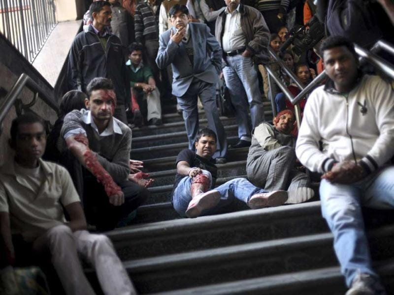 Volunteers pretending to be bomb blast victims, sit on the stairs of a metro station during a mock drill session in New Delhi. AP Photo