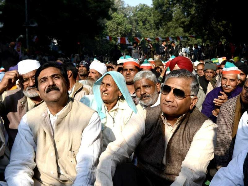 Former Army chief VK Singh (R) sits with sugarcane farmers during a protest in New Delhi. AFP Photo