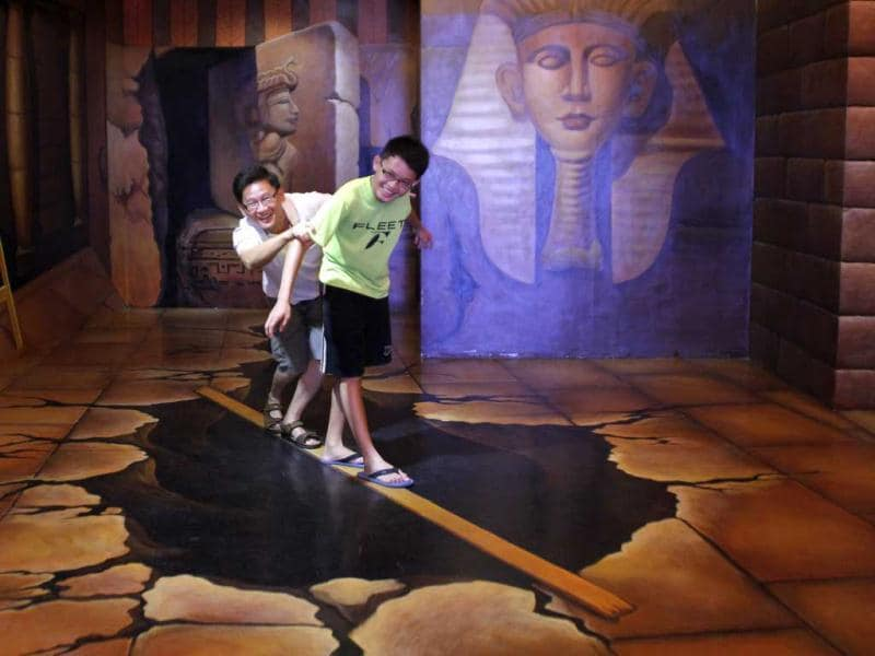 Visitors pose for a photo with a 3D artwork at Trick Art Museum in Shah Alam, outside Kuala Lumpur, Malaysia. AP Photo