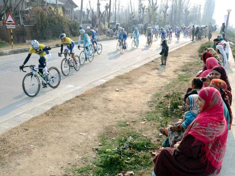 Locals watch the Tour de India International Cycling Race on the banks of world famous Dal Lake in Srinagar. It is the first ever international cycling race held in India. UNI
