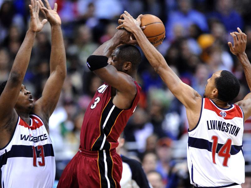 Washington Wizards' Kevin Seraphin and Shaun Livingston defend Miami Heat guard Dwyane Wade during the second half of an NBA basketball game in Washington. The Wizards won 105-101. AP/Nick Wass