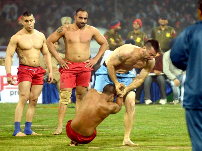 Argentina kabaddi player (2R) is tackled by his US opponent during the 3rd Pearls World Cup Kabaddi Punjab-2012 tournament at Guru Nanak Stadium in Amritsar. AFP PHOTO
