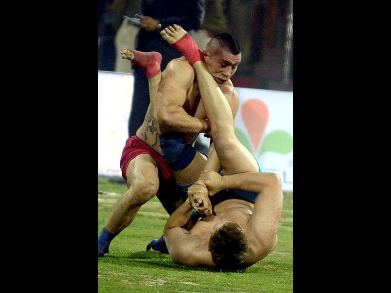 Argentina kabaddi player (R) is tackled by his US opponent during the 3rd Pearls World Cup Kabaddi Punjab-2012 tournament at Guru Nanak Stadium in Amritsar. AFP PHOTO