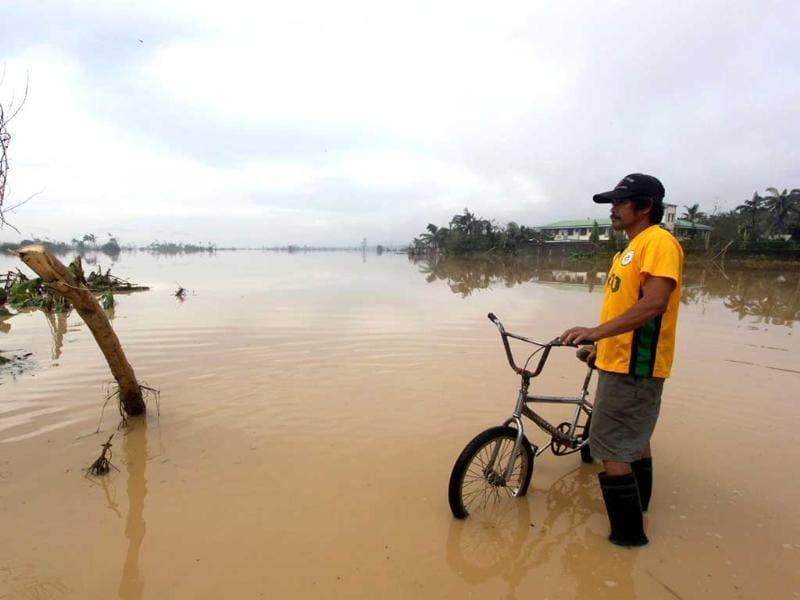 This picture shows a man with his bicycle standing in a flooded street in the aftermath of Typhoon Bopha in New Bataan, Compostela Valley in the southern Philippines. At least 325 people were killed and hundreds remain missing in the Philippines following the deadliest typhoon to hit the country this year, the civil defence chief said. AFP PHOTO / Karlos Manlupig