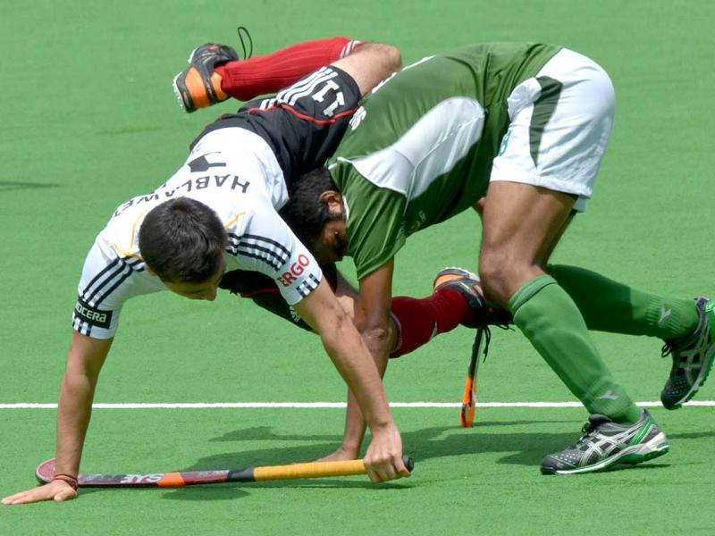 Shafqat Rasool of Pakistan pushes through Patrick Hablawetz of Germany during the first quarter final at the Men's Hockey Champions Trophy in Melbourne. AFP PHOTO