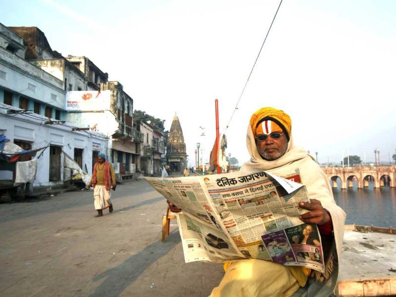 A Hindu holy man reads a newspaper on the banks of the Saryu River on the 20th anniversary of the Babri mosque demolition in Ayodhya. AP Photo