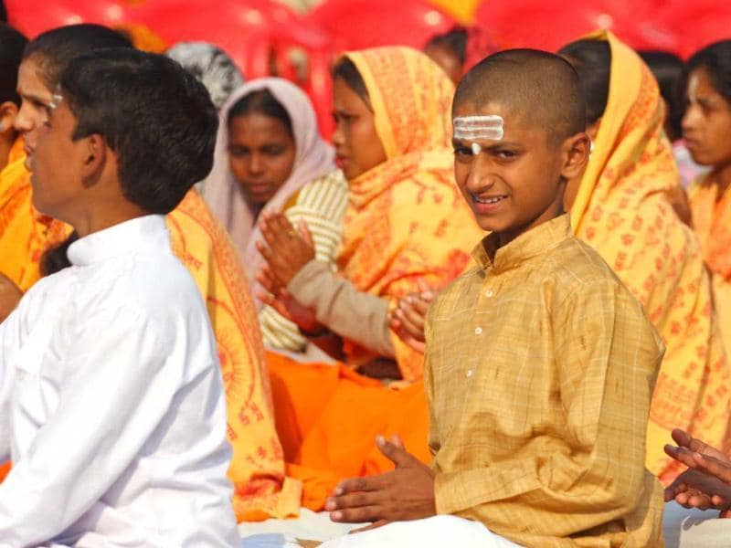 A Hindu youth of the Veda Vidyalaya looks on as he and others chant religious songs as they observe