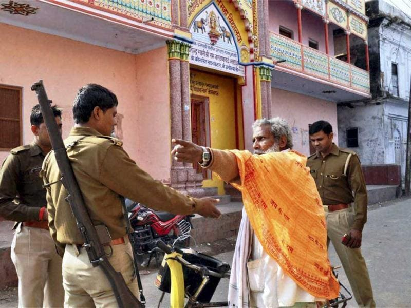 Security personnel stop a sadhu on a closed road as prohibitory orders were imposed in Ayodhya on the 20th anniversary of the Babri mosque demolition. PTI Photo