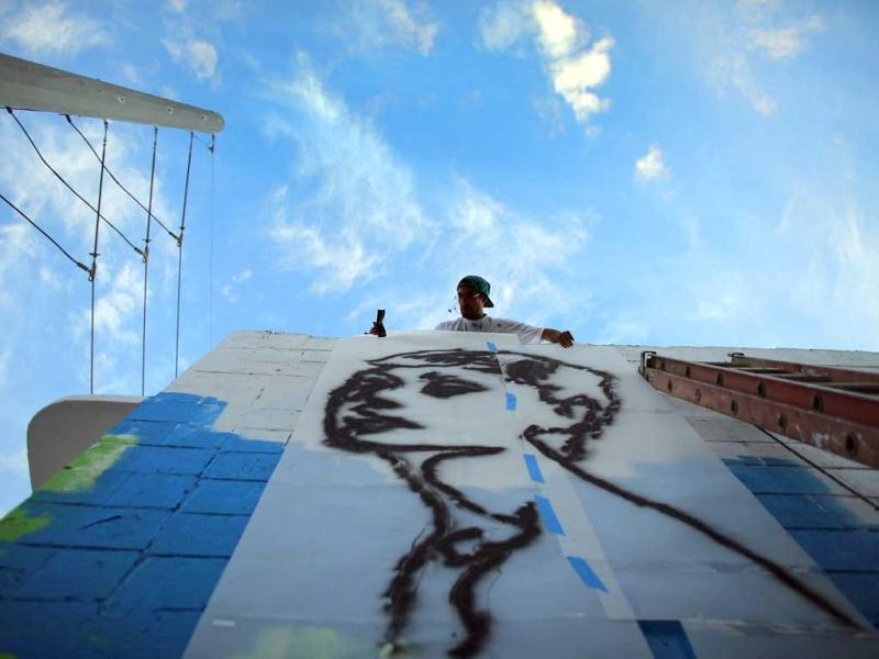 Artist known as Free Humanity works on his painting on the wall of a building as he participates in the Wynwood Walls art project in Miami, Florida. (AFP Photo)