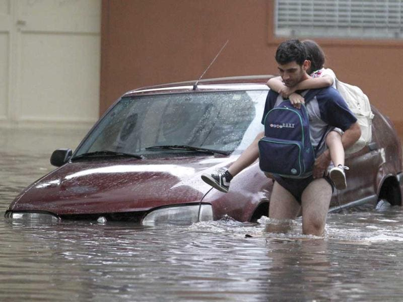 People wade through a flooded street after a rainstorm in a Buenos Aires neighbourhood. Thunderstorms in Argentina damaged property and vehicles, cut power and caused delays on flights in Buenos Aires and its suburbs as well as several provinces across the country. (REUTERS)