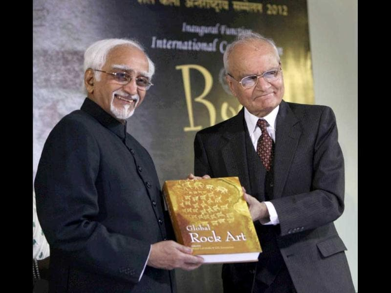 Vice President Hamid Ansari receives a book from Chinmaya R. Gharekhan, President, IGNCA Trust, during the inauguration of