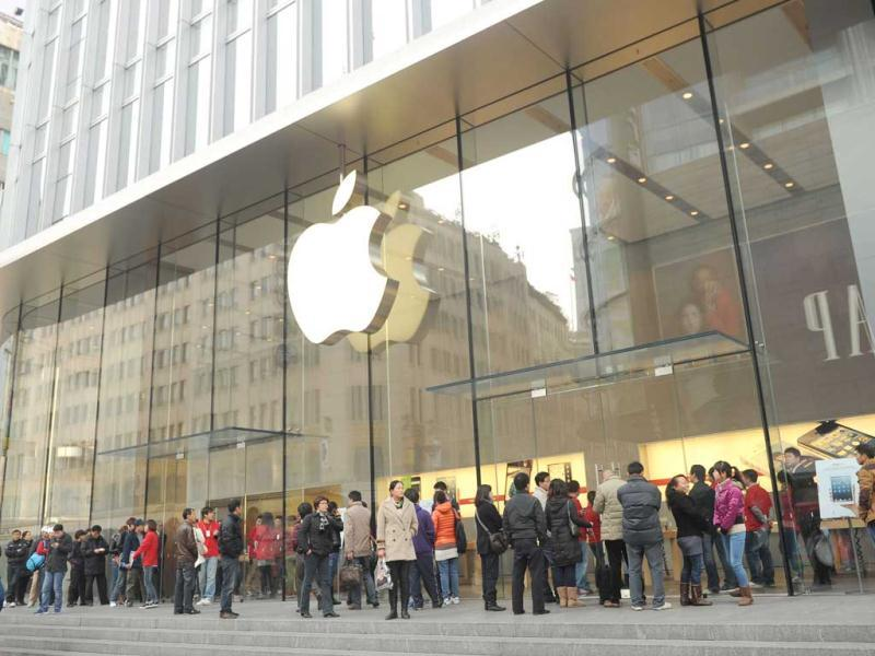 Customers wait for an Apple store to open where the new
